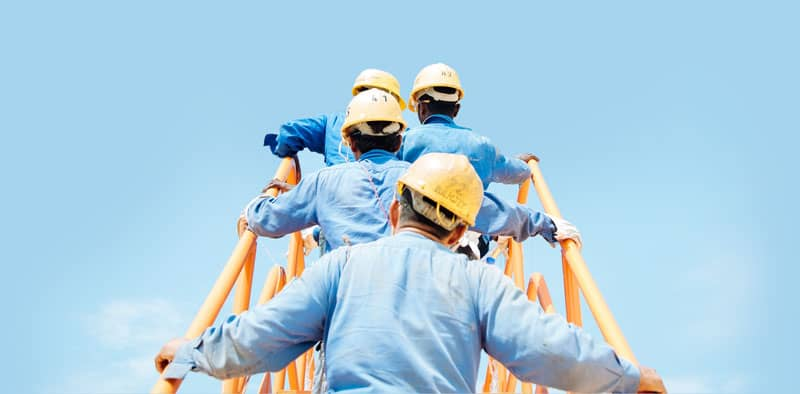people in hard hats climbing stairs